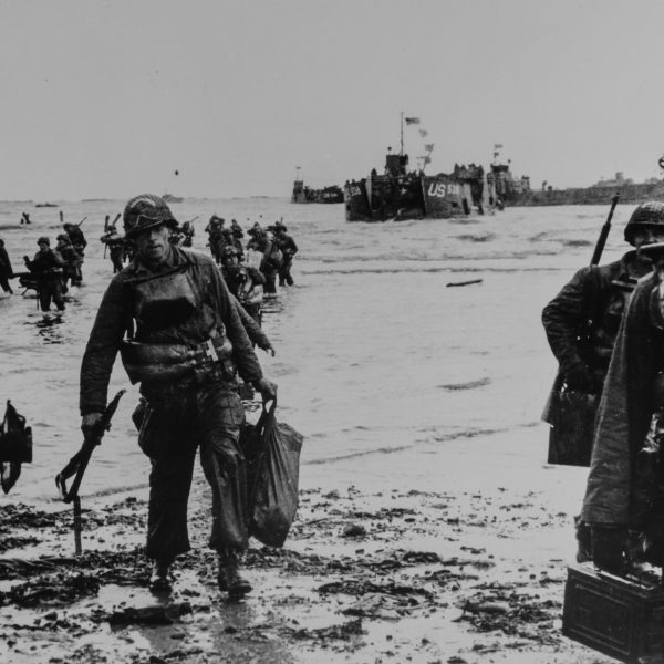 [ORIGINAL CAPTION] INVASION ... Carrying full equipment, American assault troops move onto a beachhead on the northern coast of France . Landing craft, in the background, jams the harbor. June  6, 1994. Omaha Beach.