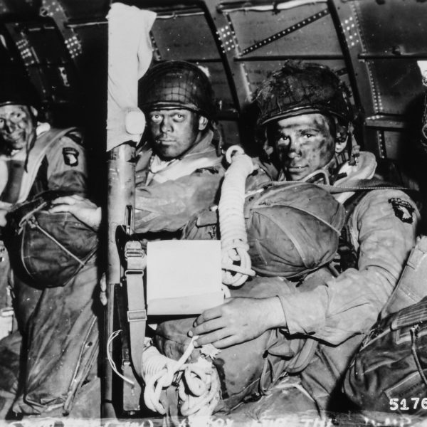 [ORIGINAL CAPTION] See You in Berlin. Resolute faces of paratroopers just before they took off for the initial assault ofD-Day. Paratrooper in foreground has just read Gen. Eisenhower's message of good luck and clasps his bazooka in determination. Note Eisenhower's D-Day order in hands of paratrooper in foreground.